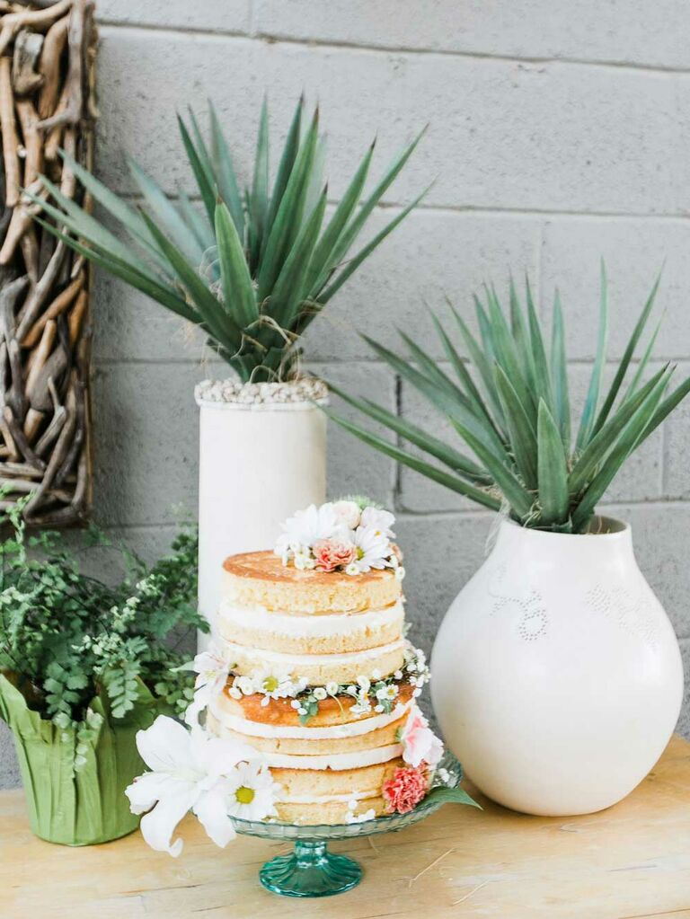 Small naked wedding cake with fresh flowers