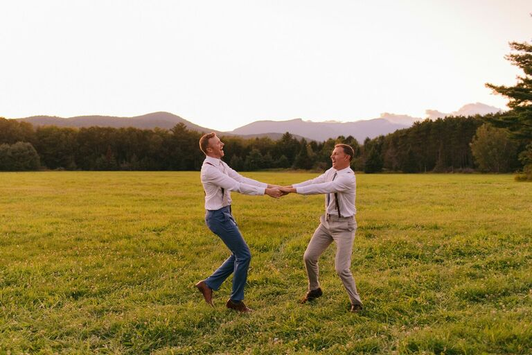 Couple twirling around in field at sunset