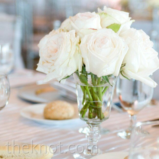 Clusters of cream roses filled vintage glass vases at the head table.