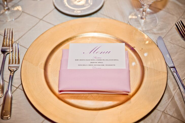 At the reception, dining tables were dressed in champagne-colored tablecloths and set with menu cards folded into pink napkins and placed on top of gold plates.