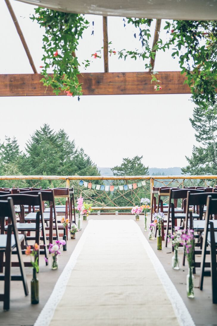 Jayme and Jeremy got married on the wooden deck at Taylor Maid Farms in Occidental, California, where they stood at the railing that overlooked miles of woodlands. Colorful blooms lined the aisle that added pops of color to the setup, and blossoms draped over wooden beams from above.