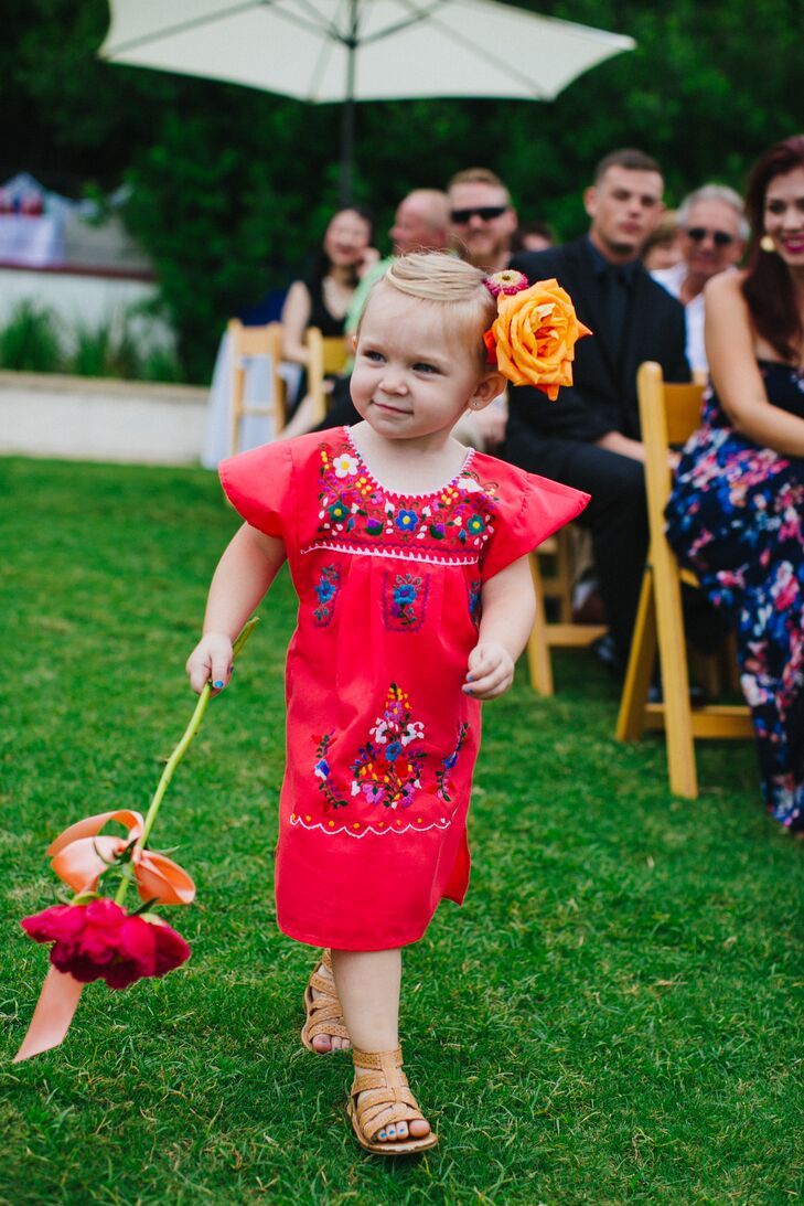The flower girl wore a bright Mexican-embroidered dress with an oversize flower behind one ear. Rather than carry a basket of flowers, she carried a single-stem bloom. The ring bearer was dressed similar to the groomsmen, complete with suspenders.