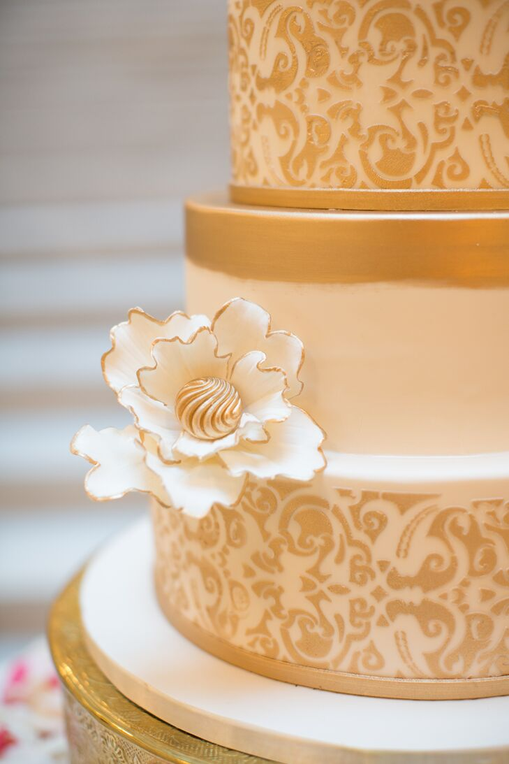 Emily and Tyler's venue, the Rookery in Chicago, Illinois, inspired their cake design—a gold and white confection covered in fondant and topped with white sugar flowers.