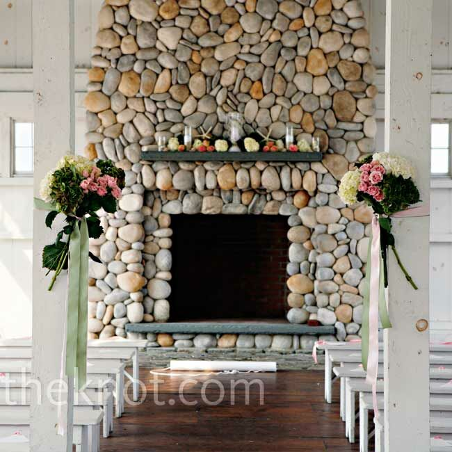 Two hand-tied bouquets of roses and hydrangeas marked the beginning of the aisle, which led to a fireplace decorated with white starfish, votive candles in sand, and fresh blooms.