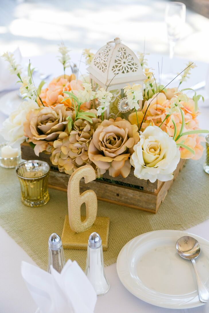 Rustic wooden boxes held arrangements of roses and hydrangeas, with a white lantern at the center.