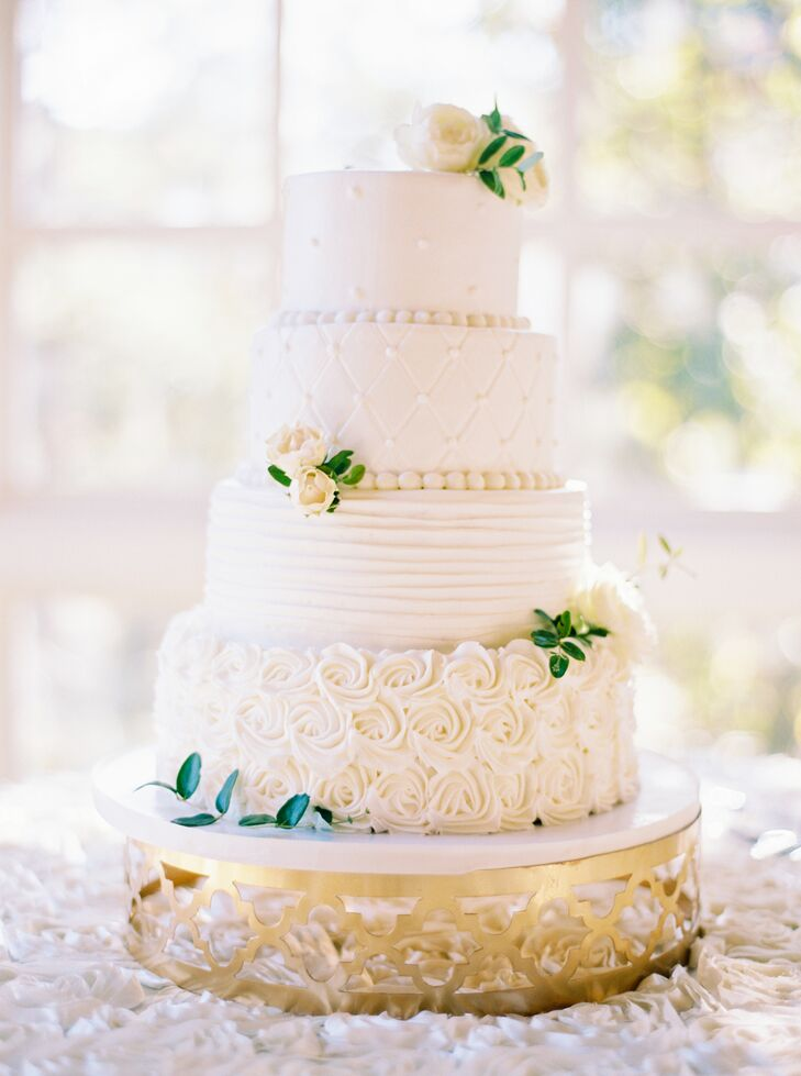 A four-tier cake with raspberry filling was frosted in almond buttercream. From rosettes to simple dots, each layer was embellished with a different design, and it was garnished with blooms and greenery.