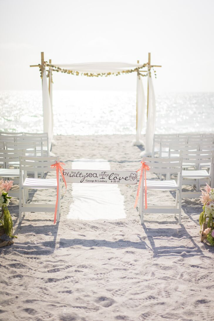 """""""The ocean has always been our favorite place. We grew to have many special moments together on the beach, including our engagement,"""" Lindsey says. """"It was no question that we wanted to have our wedding near the sea."""" The ocean was the focal point of their ceremony. They decorated the sand with only white folding chairs, a classic white runner and a few lush arrangements along the entrance. Each one was filled with blush peonies, green hydrangeas, white delphiniums, pink astilbes, white garden roses and pink roses."""