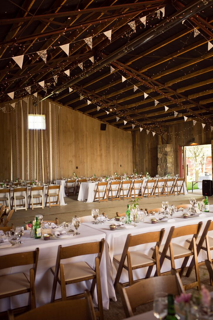 """The newlyweds used a soft color scheme of cream, champagne and blush to outfit their barn reception at Misty Farm in Ann Arbor, Michigan. """"We just knew we wanted soft colors to complement the natural beauty of the space,"""" Jo says. The bride's maid of honor even hand-sewed lace pennants that were later draped across the barn's ceiling!"""