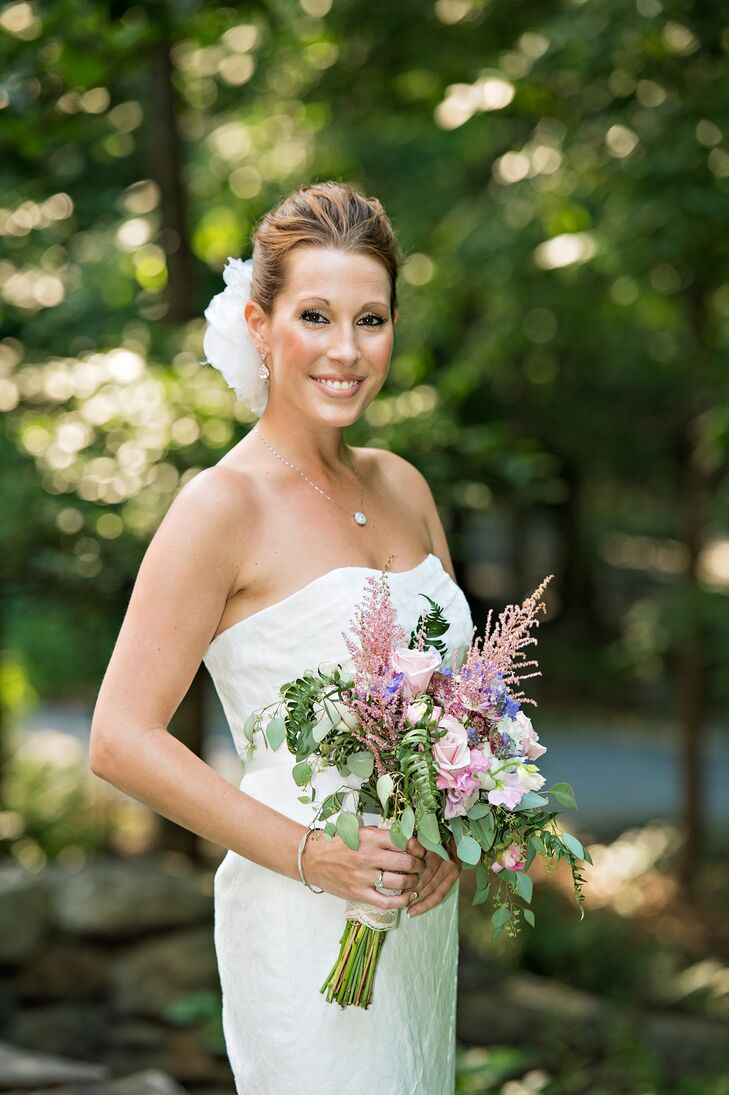 Katie wore a strapless trumpet-style gown on her wedding day. She carried a beautiful bouquet with roses, astilbe and greens.
