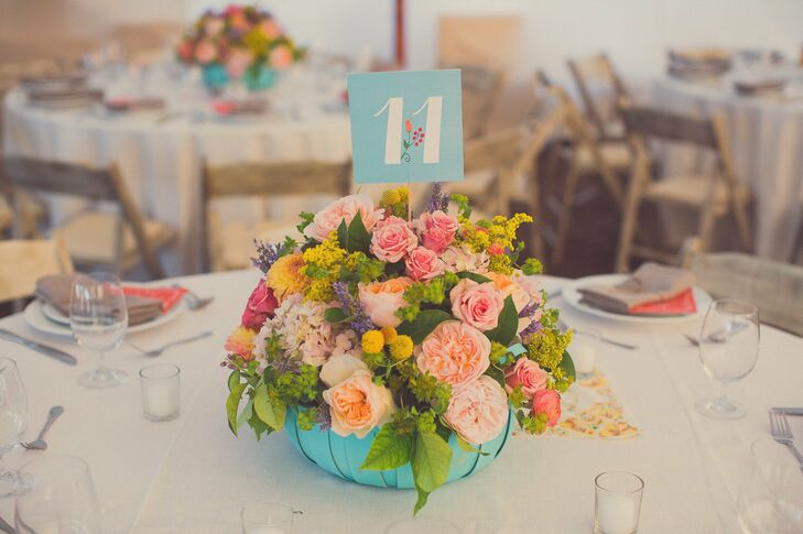Vibrant turquoise baskets were filled with peach, pink and yellow flowers, including roses, peonies, billy balls, dahlias and hydrangeas. The blue and white table numbers had graphic prints that matched the couple's programs.