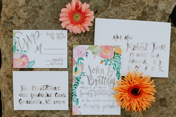 "Invitations were adorned with artfully painted watercolor florals and greenery as well as flowing gray cursive font. ""We are both artists and wanted to incorporate our personal touch,"" Christian says."