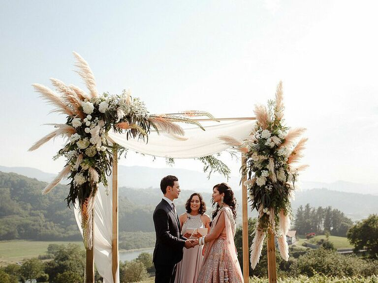 Bride and groom reciting vows in front of statement floral arch with dried flowers and pampas grass