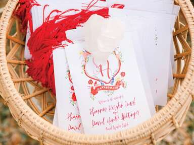 red and white ceremony programs with watercolor monogram crest