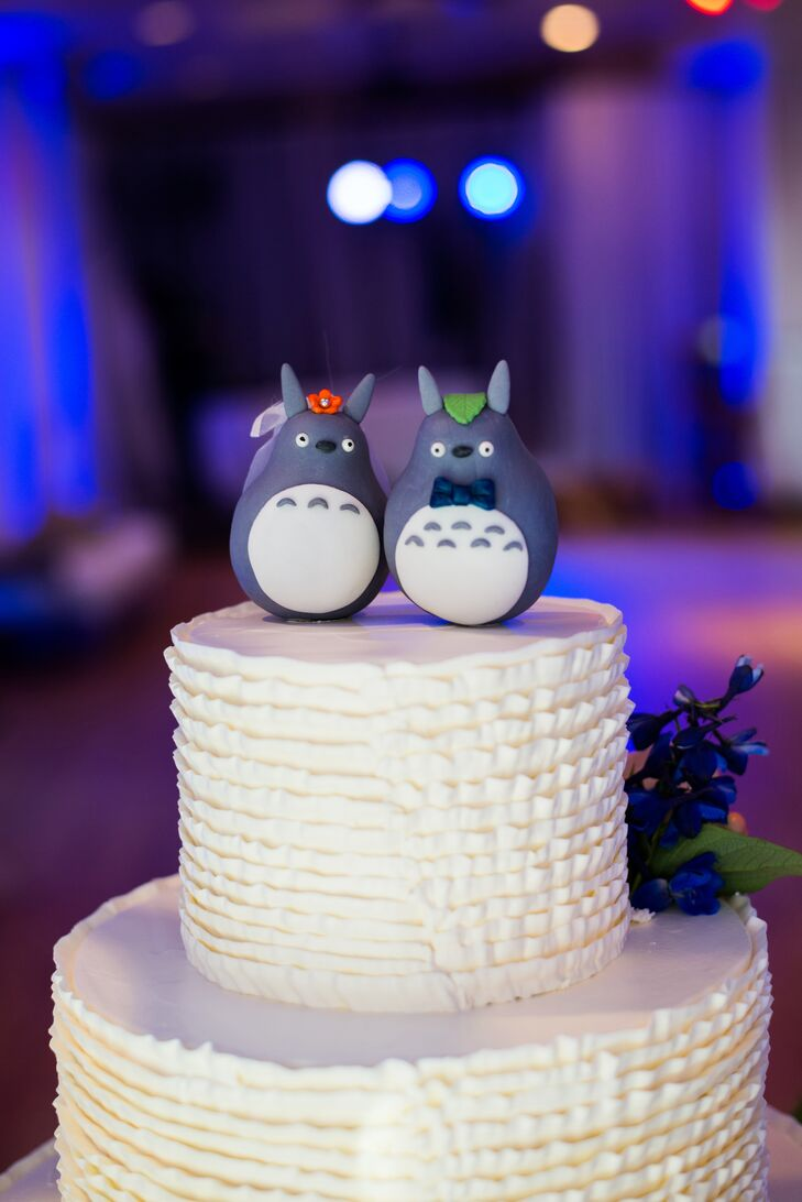 """The couple had a custom Totoro cake topper, inspired by Hayao Miyazaki's animation """"My Neighbor Totoro."""" Matt has done kendo from a young age, so the couple cut their wedding cake with one of his swords."""
