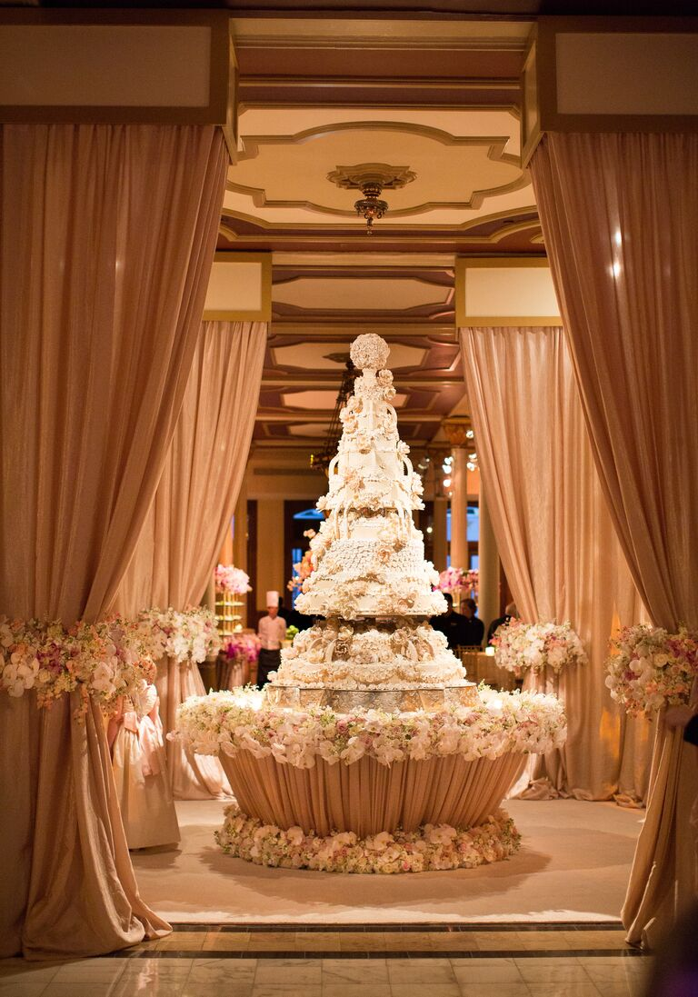 Grand white wedding cake with custom floral designs
