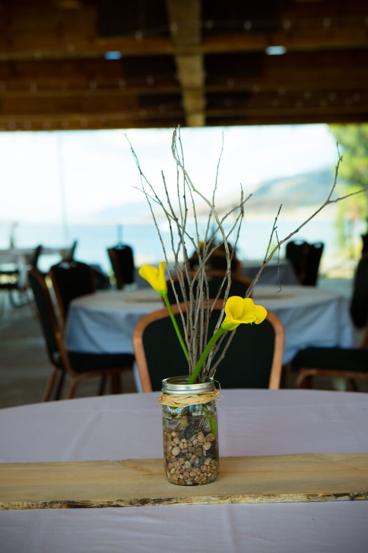 The reception tables were decorated with a wooden table runner topped with mason jars filled with river rocks and aspen branches from the surrounding forest, which were completed with yellow calla lilies.