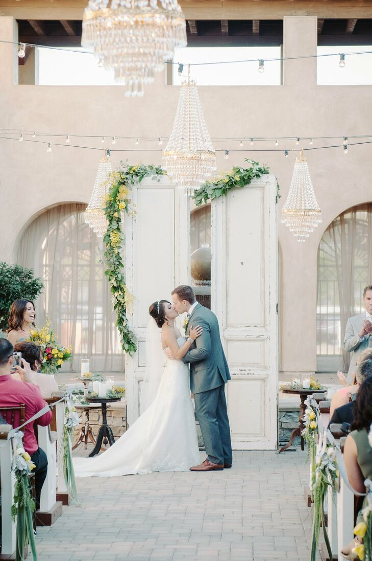 The ceremony backdrop was comprised of two vintage chapel doors draped with a yellow floral and lemon leaf garland and crystal chandeliers that gave the outdoor a hint of elegance and formality.