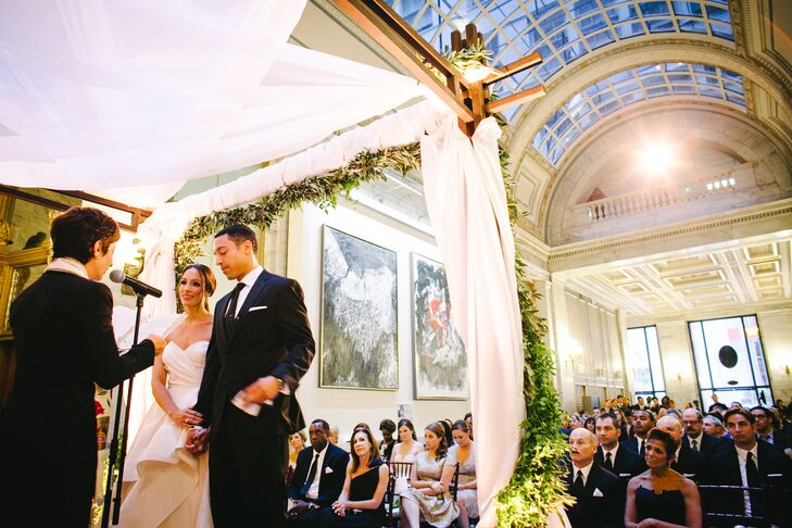 The couple were married underneath a white chuppah that was decorated with green garland at the ceremony.