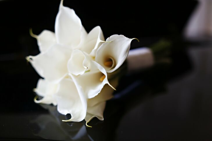 The bride's bouquet  was full of white calla lilies and wrapped in satin ribbon.