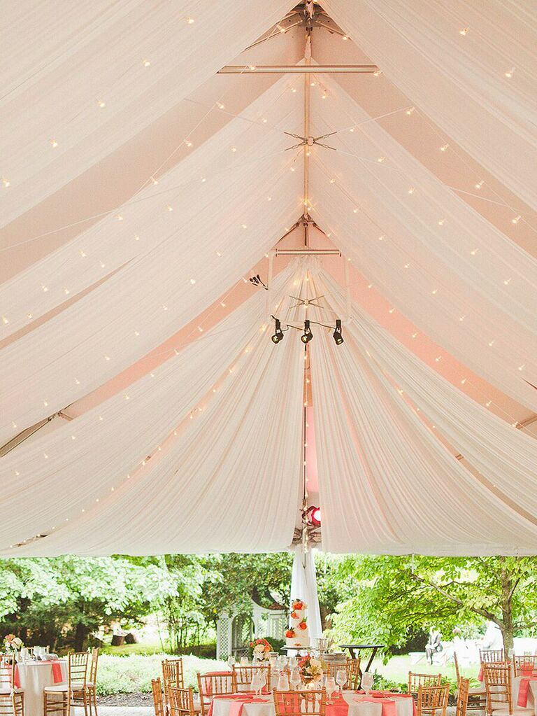 Classic wedding tent with draped ceiling and string lights