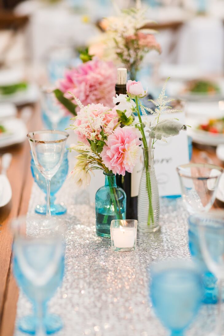With the help of Melissa Stewart of Artistry Catering & Events, Jennifer and Nick brought a little big-city flair to the quaint New England farm in Lexington, Massachusetts. The couple chose an industrial, rustic theme, combining sleek metallic elements and shimmery accents with wooden furnishings, antiques and burlap accessories. A palette of bright pink, blue, purple and ivory introduced a layer of softness to the decor, while travel-inspired details added a touch of playfulness and personality.