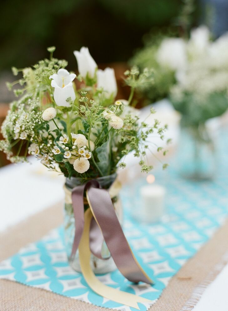 Textured bunches of white flowers sat on top of colorful, custom table runners.