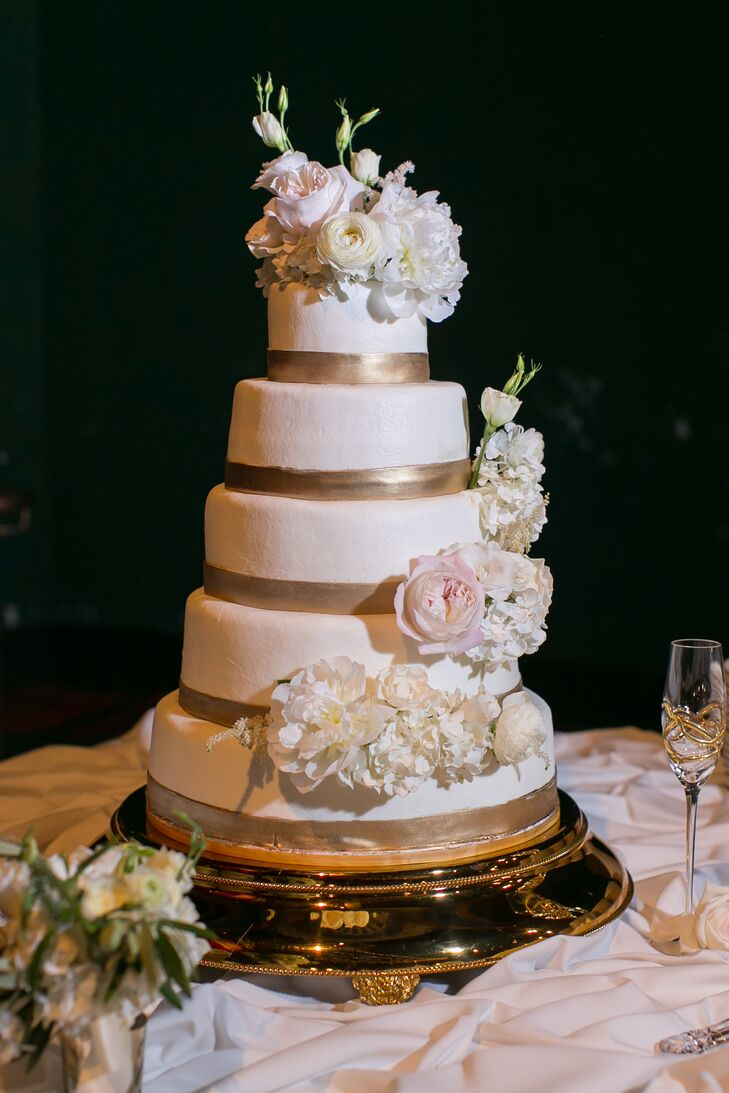 For dessert, Allie and Liam enjoyed a five-tier white buttercream wedding cake. Each layer was decorated with gold detailing at the bottom to match the glam palette. White peonies, white hydrangeas and blush roses added plenty of romance to the confection.