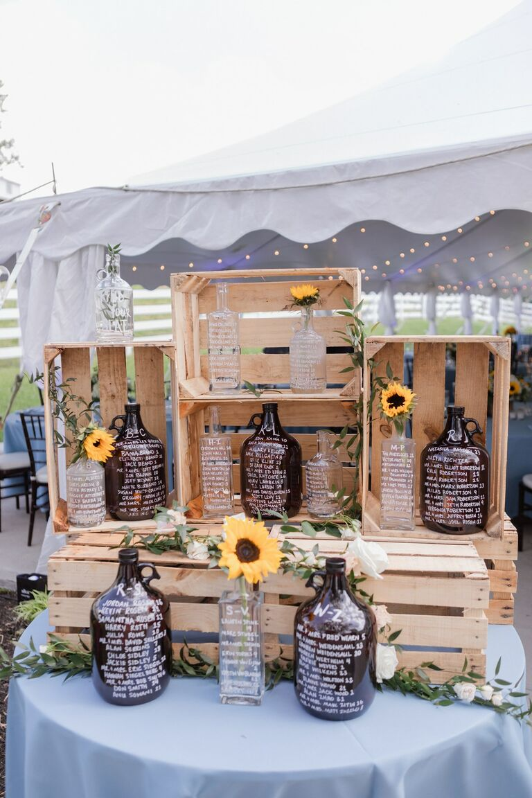 Wood crates with glass growlers for seating chart display
