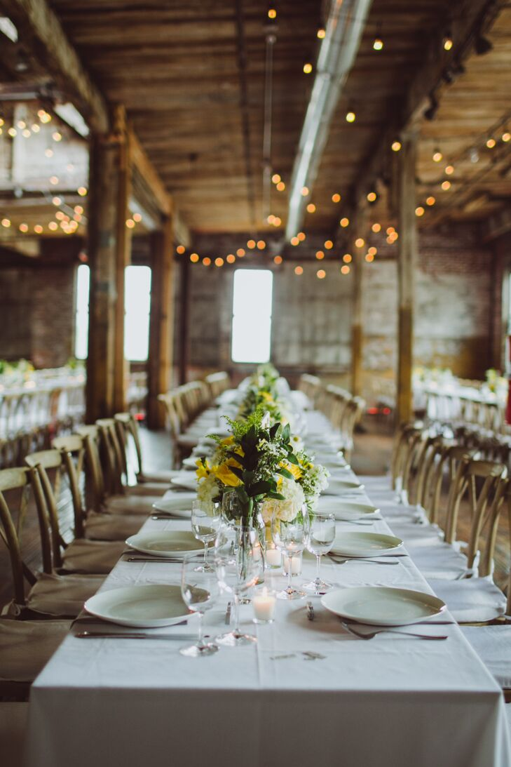 For the reception at the Greenpoint Loft, the couple kept the decor simple, letting the venue's features take center stage. Long farm tables draped in white linens were styled alongside cross-back chairs and bundles of brilliant yellow and green blooms. Twinkling bistro lights hung overhead, casting a warm, ambient glow over the expansive loft space.