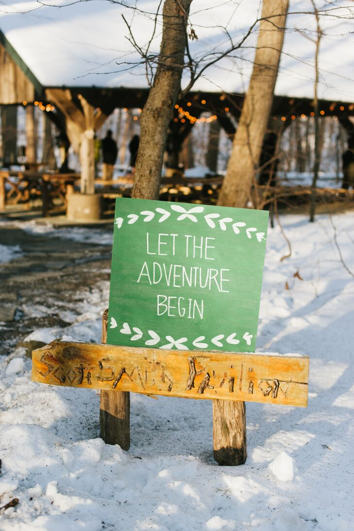 "As guests walked toward the wooden pavilion for the ceremony, a green sign with white designs and text greeted them. The welcoming sign read ""Let the Adventure Begin."""