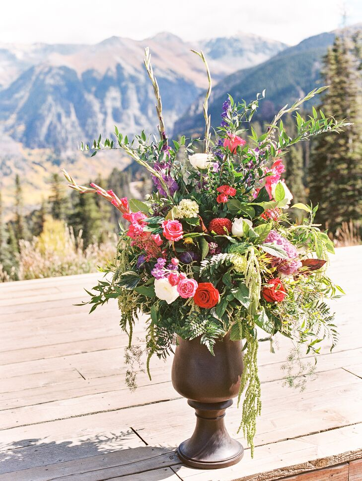 Vibrant floral arrangements with lots of greenery and crimson and pink blossoms followed a less expected palette for this fall mountain wedding.
