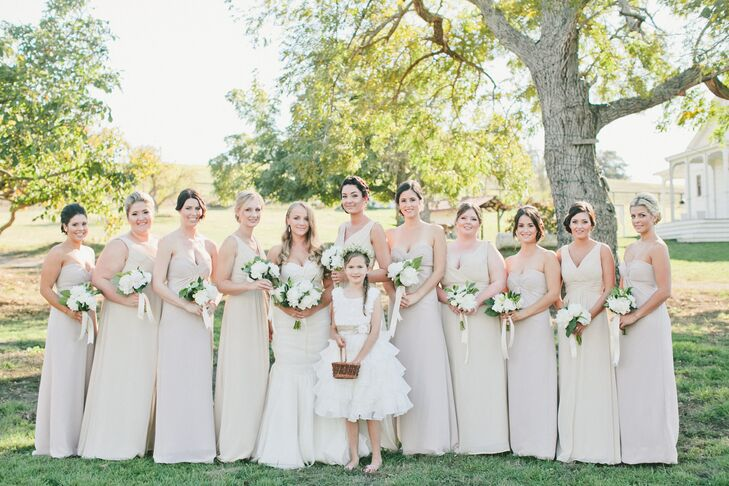 The bridesmaids followed the soft neutral-colored palette with their long dresses in different shades of white. They all held bouquets filled with white blooms and greenery, just like the bridal bouquet.