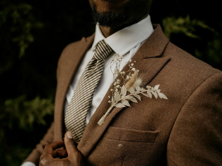 Groom wearing neutral brown suit with dried floral boutonniere