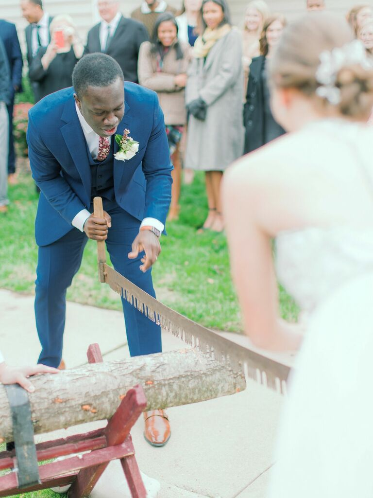 Couple sawing log during wedding ceremony