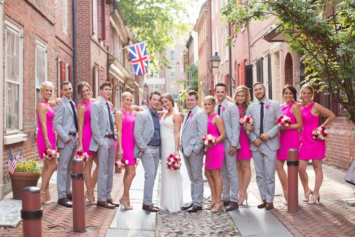 """Everyone in the wedding party accented the summer season with a short looks. The bridesmaids sported hot pink cocktail-length dresses with matching pink and white rose bouquets. For the men, Chad had them suit up in blue seersucker suits. Instead of boutonnieres, they all wore hot pink paper flowers from Etsy on their lapels. """"They were so fun and different,"""" Mari says."""