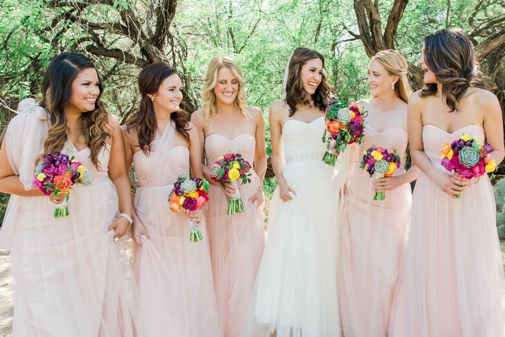 """Kelsey's bridesmaids donned floor-length, tulle dresses that were a very light dusty rose. """"The dress had tulle straps that could be fashioned in a number of ways, so they could all customize their dress to their body type and desire,"""" she says."""