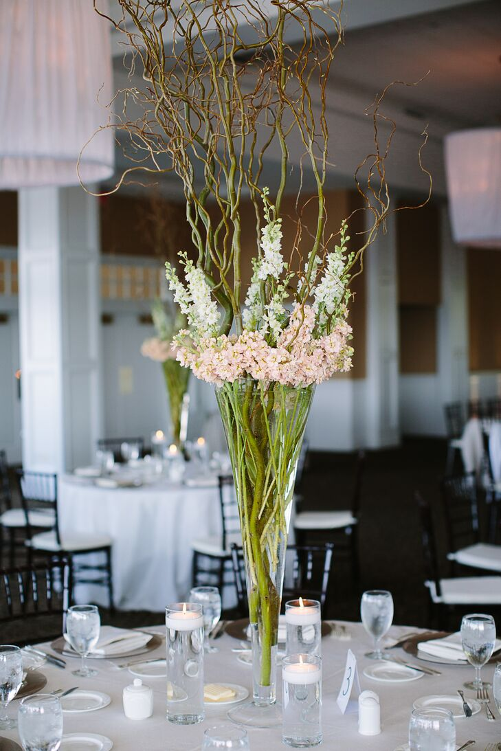 Each of the glass centerpieces held tall white and blush linaria flowers. Branches gave the pieces extra height.