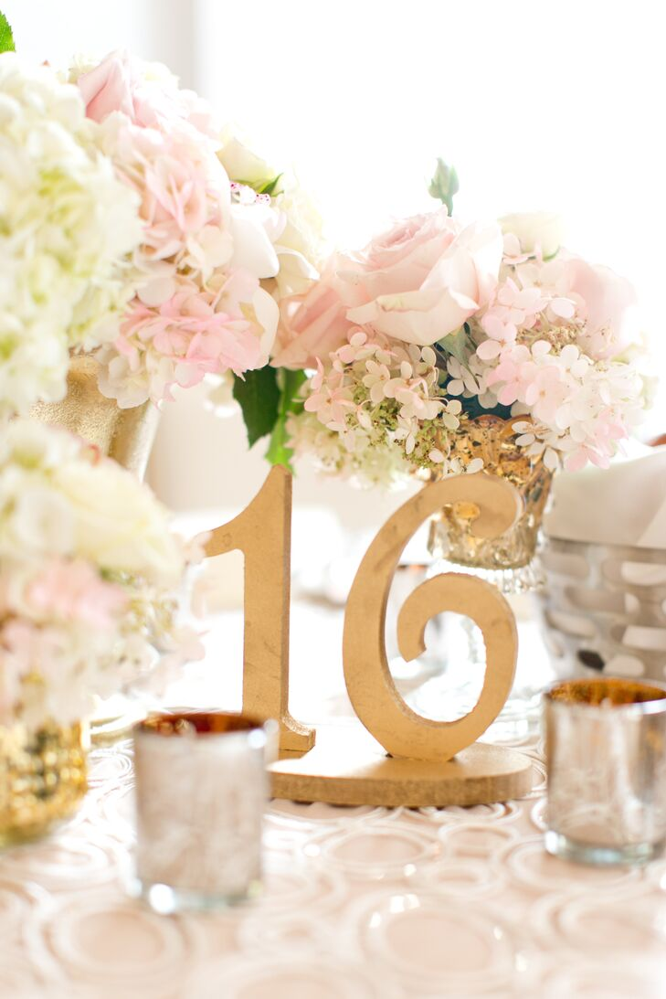 Table numbers were gold cutout markers surrounded by delicate roses and baby's breath. Small votive candles highlighted each table.