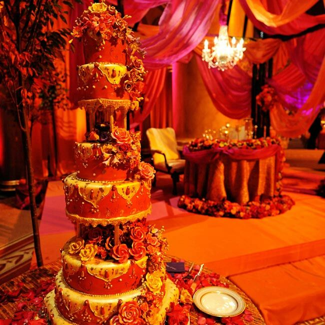 The regal, seven-tier cake was made to match Dolci's fabulous, red reception gown. Scarlet, white, gold and purple sugar flowers trailed down the cake, and little gold accents echoed the design of the bride's jewelry.