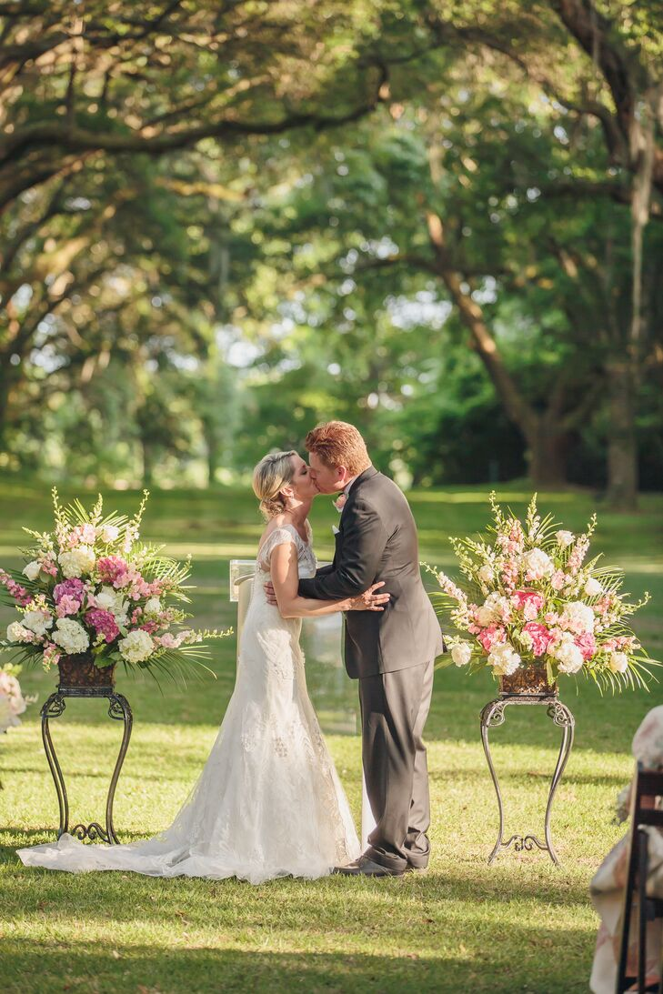 The outdoor ceremony site was decorated with pink and white floral arrangements in square brass vases. Heather and David loved how the lush flowers added an English garden feel to the spacious, outdoor location.