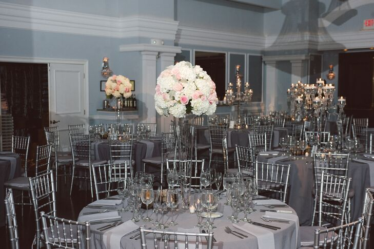 The centerpieces consisted of dome-shaped ivory and blush floral arrangements on tall, transparent vases.