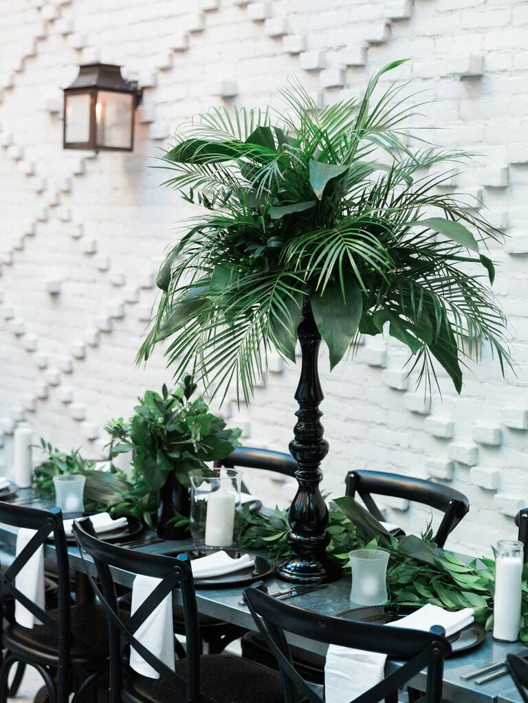 Lush tropical palm leaves as reception centerpieces in sleek black vases