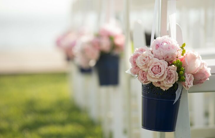 Small navy-blue pails filled with pink peonies and roses hung at the end of every other row of chairs at the ceremony.