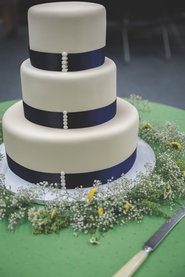 The white wedding cake banded with navy at the bottom of each layer stood three tiers tall and was placed on a simple stand, which was surrounded by a ring of baby's breath and yellow button mums.