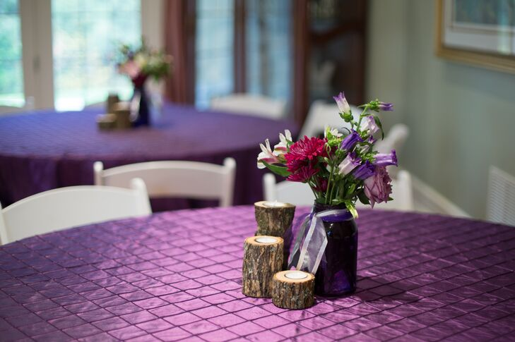 Centerpieces at the reception consisted of small wooden slabs and flower arrangements of fuschia chrysanthemums and pink and purple lilies.