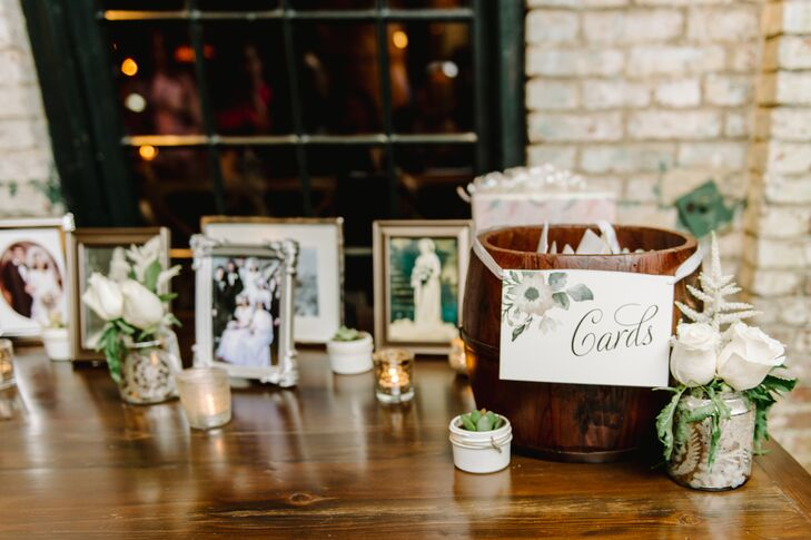 Guests placed cards inside the wooden barrel marked with a watercolor design, positioned next to family photos in vintage frames, mercury glass votive candles and tiny potted succulents.