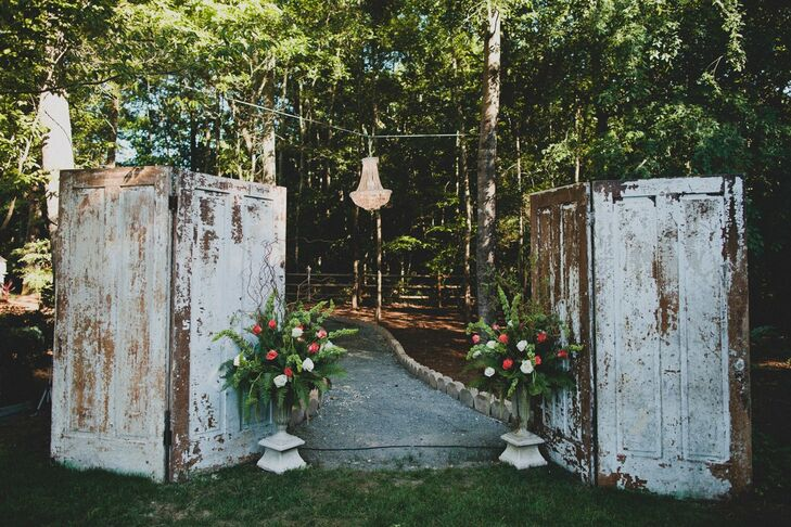 Two vintage old white doors were at the end of the aisle that framed where we got married. We also hung a large chandelier between the two doors. Two large pots of flowers on the ends of the doors became the entryway for the walkway that my groom, officiate, and best man entered from behind. There were orange, coral, pink, and white roses with hanging armarthus to give the area a vintage garden look.