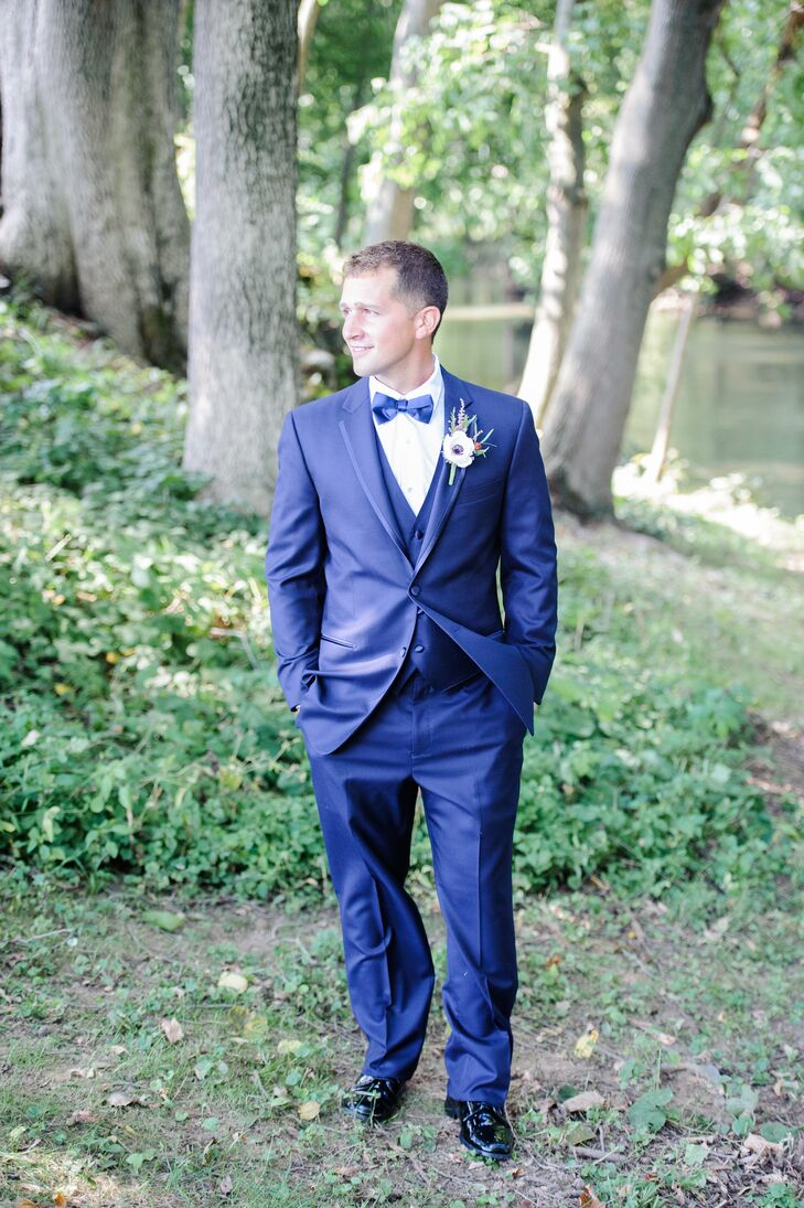 Instead of the traditional black tux, Ryan wore a fitted navy tuxedo with a navy bow tie from Men's Wearhouse. His groomsmen also wore navy tuxedos, paired with a wine-colored bow tie.