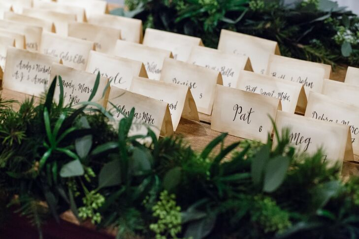 For the escort cards, Lily turned to her friend and bridesmaid from Merely Mere. She designed the stationery and gave it that vintage feel by hand-dipping each one with tea bags. Then she used her practiced skill in calligraphy to give them an added elegant flair. Lush greenery surrounded each row to tie in their forest-like theme.