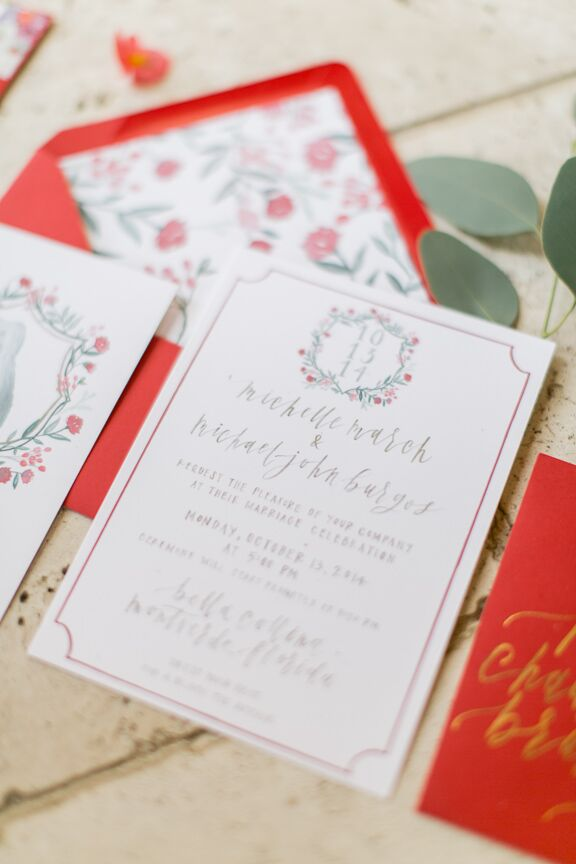 "The couple worked with Juliet Grace Design to create a custom  family crest for their invitation suite. Their dog, Joy, was placed at the center, surrounded by the couple's last name and wedding date. ""Joy had the flowers surrounding her. We really used that as the main inspiration for style and colors,"" says Michelle."